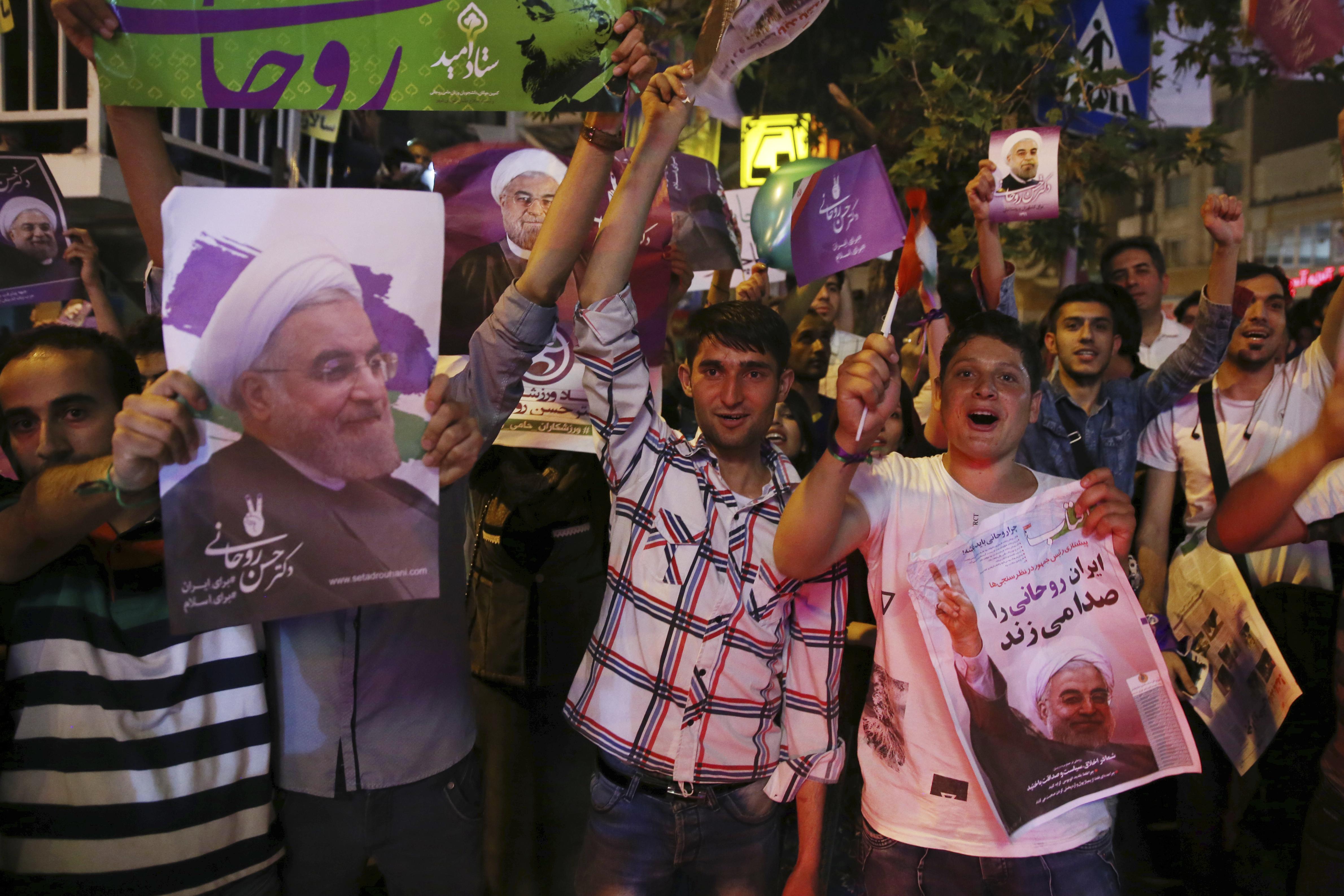 伊朗民眾拿著候選人魯哈尼的相片在德黑蘭街頭表達支持。(美聯社)