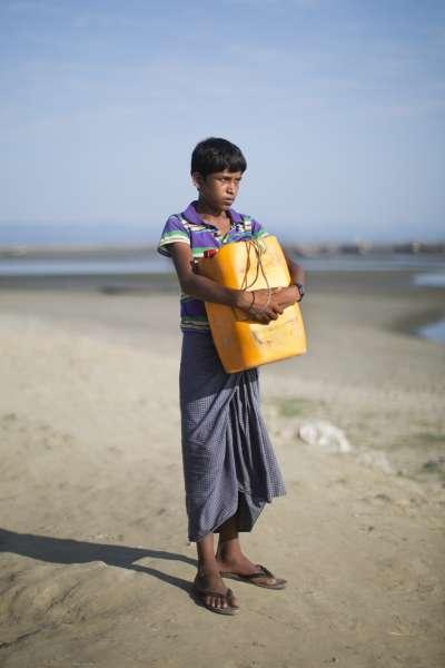 11月3日,13歲的羅興亞難民納比靠著一只黃色塑膠油桶渡過納夫河,從緬甸逃到孟加拉(AP)