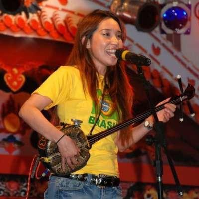 歌手古西(Megumi Gushi)彈三弦琴,用沖繩語演唱。(BBC中文網)