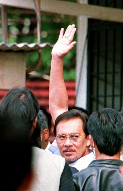1998年9月,安華被解任副總理與財政部長職務後面臨雞姦案官司,他在走入法庭前回頭向支持者回頭揮手致意。(美聯社)