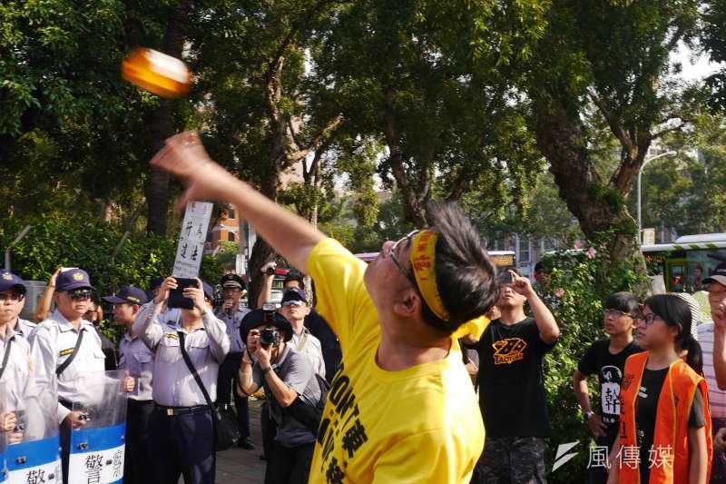 反南鐵東移自救會赴政院抗議,陳致曉丟小豬撲滿。(洪與成攝)