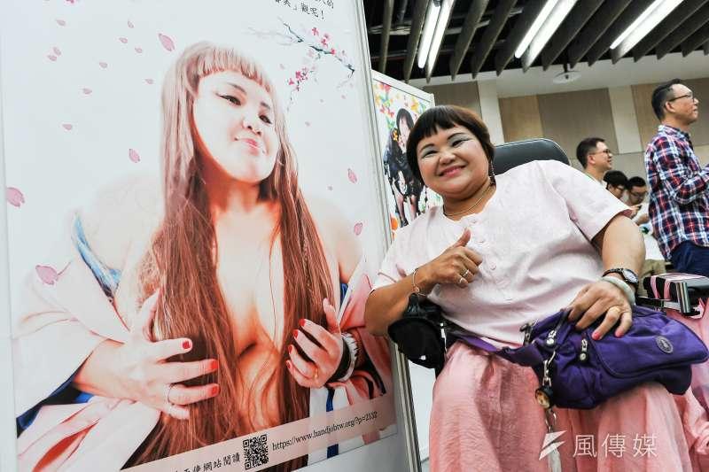 「礙美・愛美」座談會暨攝影作品成果展,於8日在台北市大同中山身資中心舉辦。圖中為身障朋友劉玟玲與自己作品合照,表情相當開心。(甘岱民攝)