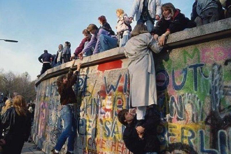 「喪失是逐步的。但是我選定的那一刻,是柏林圍牆塌垮的當下,喪失似乎最尖銳。」(圖為大批東德民眾翻過柏林圍牆的一刻。資料照,中評社)