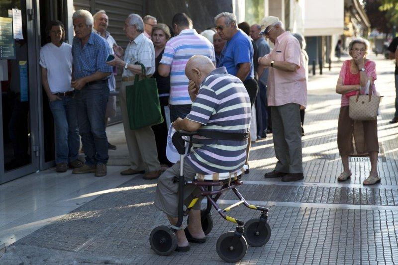 希臘崩潰後,退休所得替代率由9成降成6成,台灣別搞到財政崩潰再思改革。圖為希臘老人家排隊領取賴以維生的退休年金(美聯社)