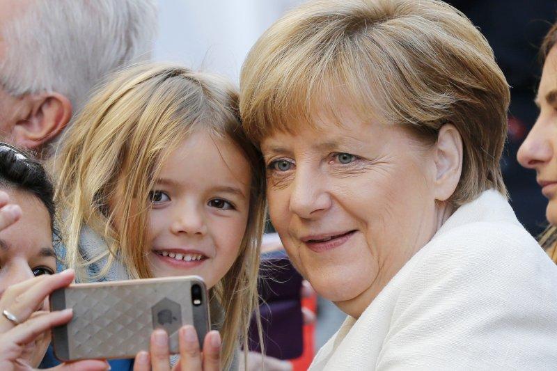 德國總理梅克爾(Angela Merkel)在慶祝兩德統一的活動上與小女孩合影(美聯社)