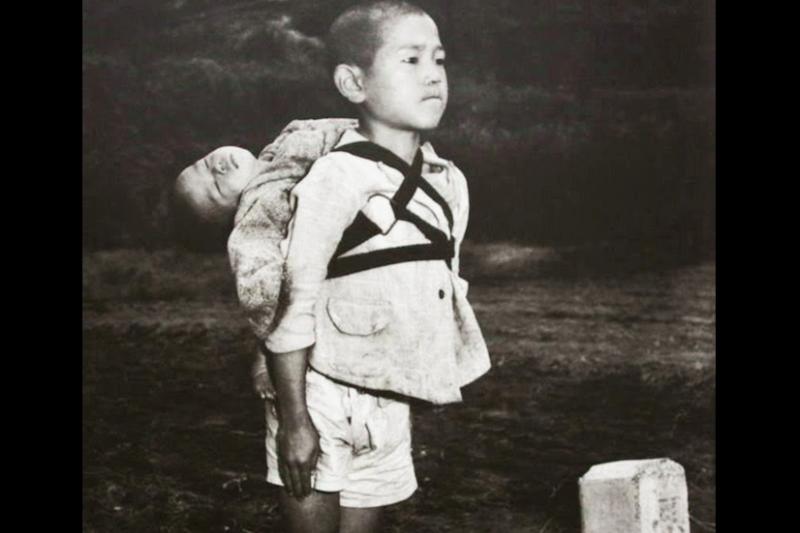 男孩直挺挺地站著,背上的娃兒已經了無氣息⋯⋯。(圖/RareHistoricalPhotos)