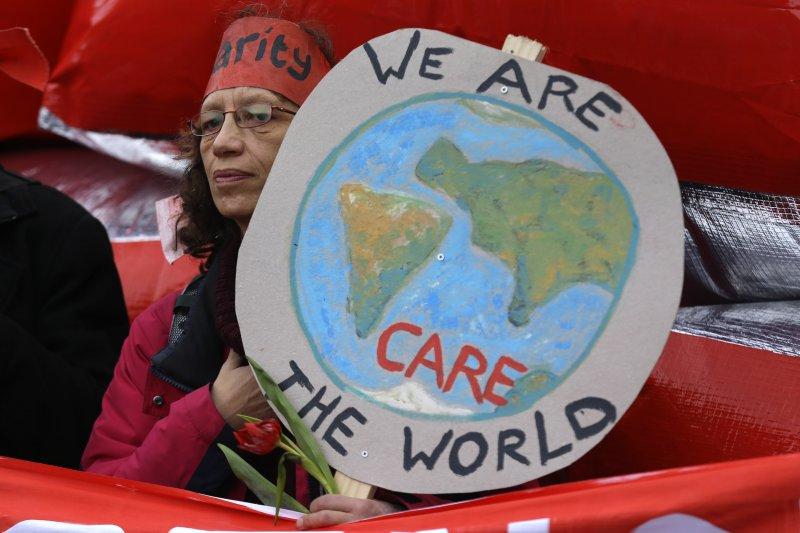 去年「巴黎氣候峰會」場外民眾舉著標語。(美聯社)