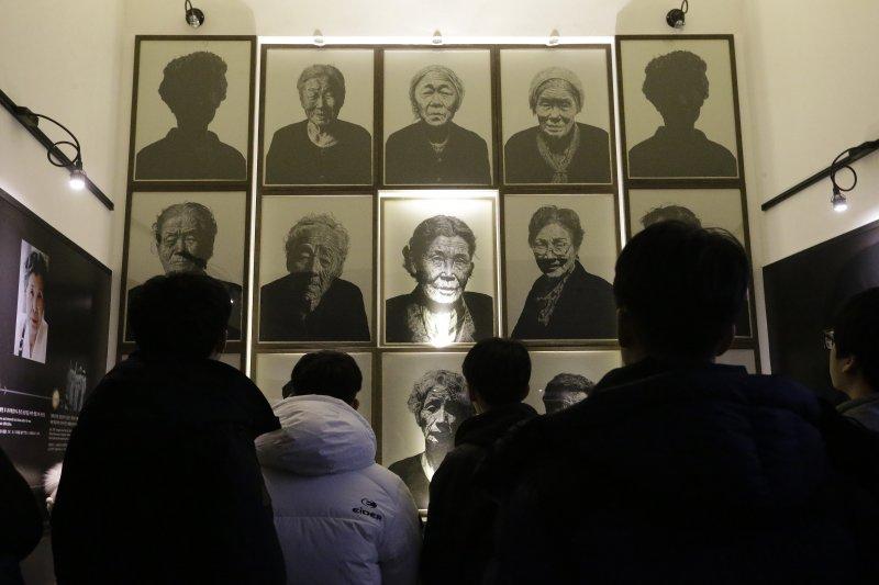 南韓的高中生在京畿道廣州市的「分享之家」觀看已過世的慰安婦阿嬤照片。(美聯社)