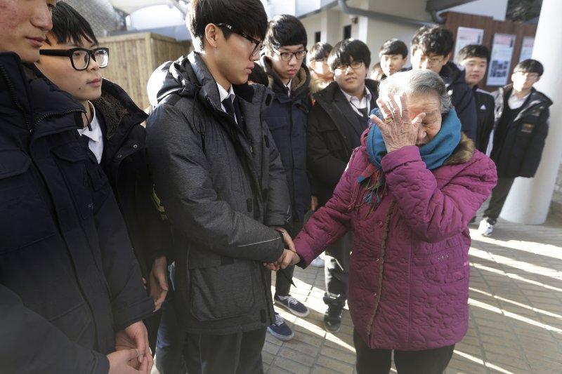 南韓高中生到京畿道廣州市的「分享之家」探望曾擔任日軍慰安婦的阿嬤。老婦牽著高中學生的手,頻頻拭淚。(美聯社)