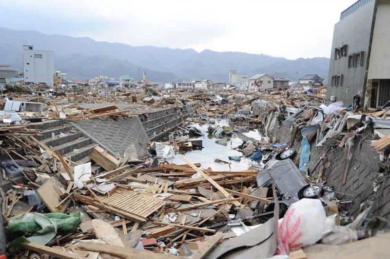 311大地震後,日本岩手縣大船渡市被海嘯破壞四散的房屋和汽車。(維基百科)