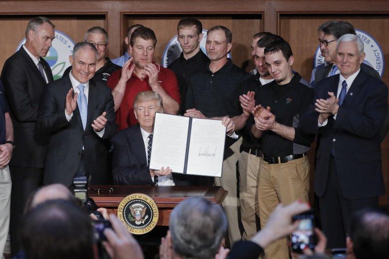 川普在幕僚與一群礦工簇擁下,簽署了行政命令,推翻歐巴馬環保政策。(美聯社)