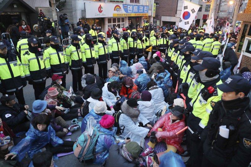 朴槿惠的支持者在三成洞的朴宅附近抗議,警力將其包圍以免滋事。(美聯社)