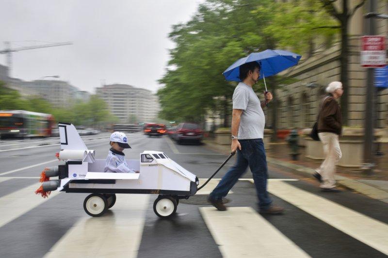 全球逾600城市響應「科學進軍」活動,1名爸爸帶著孩子在華府參加遊行(AP)