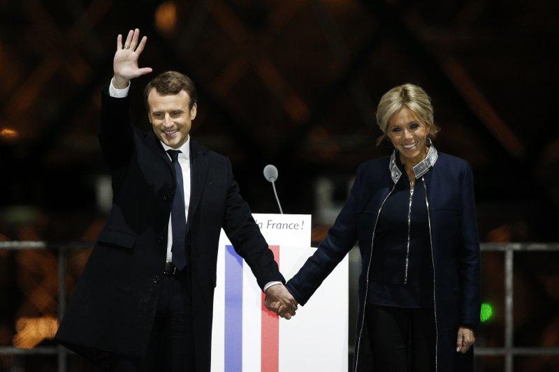 法國總統大選第二輪決選7日(台灣時間8日凌晨)揭曉,中間派候選人馬克宏當選總統,與妻子布莉姬特接受支持者歡呼(AP)
