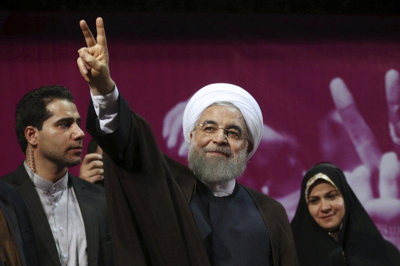 伊朗總統候選人魯哈尼對群眾比出勝利手勢。(美聯社)