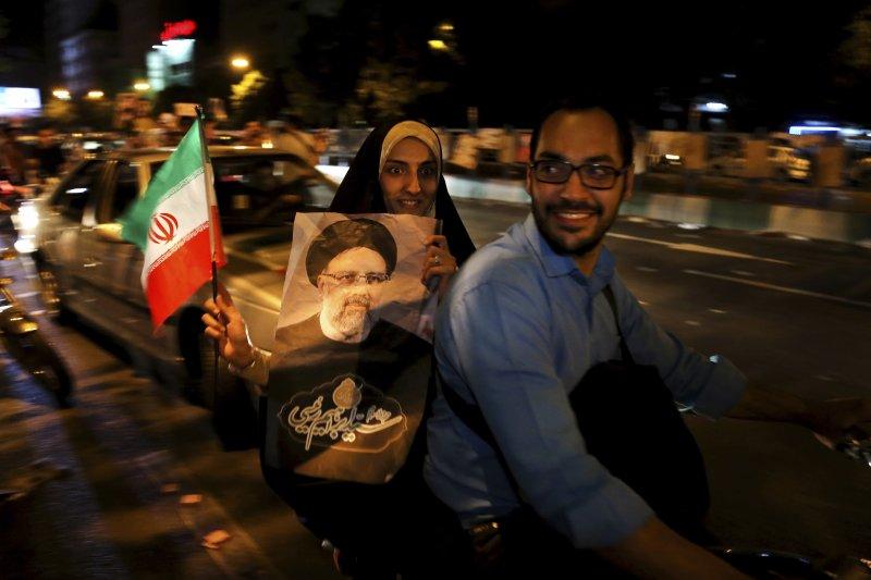 伊朗民眾拿著候選人萊希的相片在德黑蘭街頭表達支持。(美聯社)