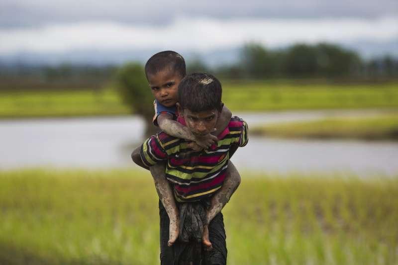 一個羅興亞的小男孩背著自己的弟弟,走向逃難的行列。(美聯社)