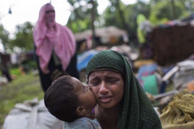 緬甸軍隊加強掃蕩,許多羅興亞穆斯林逃往邊境,一名孩童在逃難過程親吻媽媽。(美聯社)