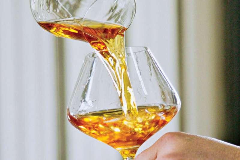 釀酒師陳千浩在勾兌不同年份的黑后及金香桶陳酒液,融合老年份香甜圓潤、新年份清新酸度等不同特性,以達最佳口感。(攝影者.陳平卿)