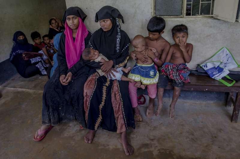 9月13日,剛抵達孟加拉難民營的羅興亞婦女抱著孩子在人道援助組織開設的醫療站外等待(AP)