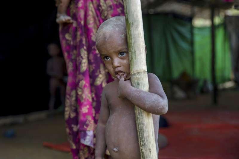 9月13日,剛從緬甸逃到孟加拉巴拉卡里(Balukhali)難民營的一位小男孩站在剛建好的簡陋住處前(AP)