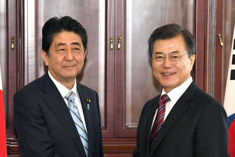 「日本和韓國在這場『北韓核彈遊戲』裡,注定會成為輸家。如果日本不去正視這個現實的話,將無法找出適當的解決方案。」圖為安倍晉三與文在寅。(資料照,美聯社)