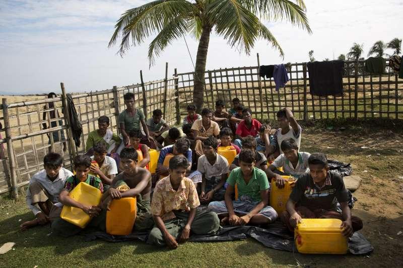 11月4日,一群羅興亞男子靠著黃色塑膠油桶渡過納夫河逃到孟加拉,等待被轉送到難民營(AP)