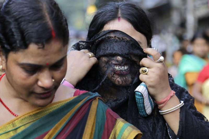 印度加爾各答「索納加奇」紅燈區的一名性工作者以黑紗遮住臉(AP)