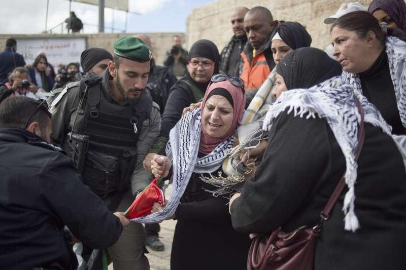耶路撒冷舊城區的以色列警察試圖搶走一名巴勒斯坦婦女手中的國旗。(美聯社)