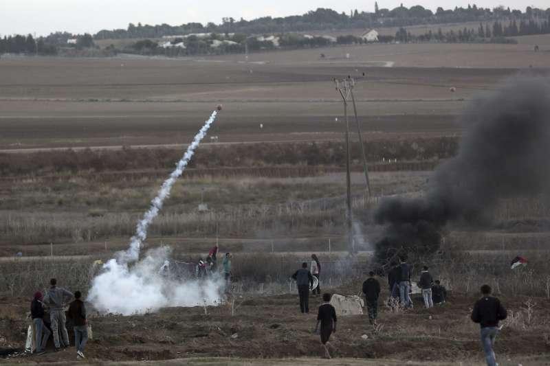 加薩走廊的巴勒斯坦抗議者將以色列發射的催淚彈擲回以方。(美聯社)