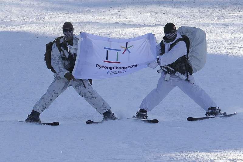12月19日,美軍與南韓軍方在平昌舉行冬季聯合軍演,一名南韓軍人與一名美軍拿著平昌冬奧的旗子(AP)