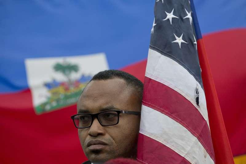 川普屎坑說:海地移民舉著美國國旗,背後為海地國旗(AP)