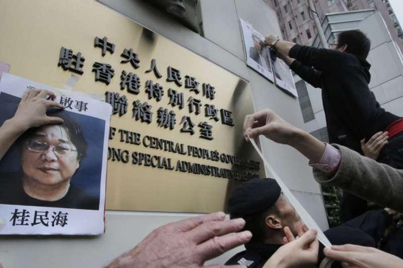 香港民眾在北京駐香港機構中聯辦前高舉銅鑼灣書店老闆桂民海的肖像,要求中國政府釋放桂民海。(美聯社)