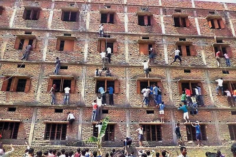 圖說:印度作弊風氣猖獗,2014年一群家長爬上建築物外牆,幫助考生作弊。(AP)