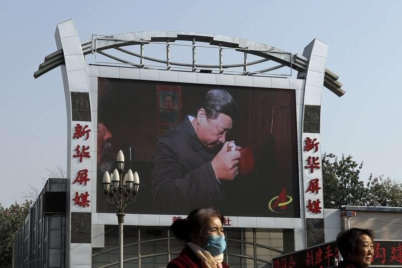 北京的火車站旁,正播放著習近平拜訪中國農村的紀錄片。(美聯社)