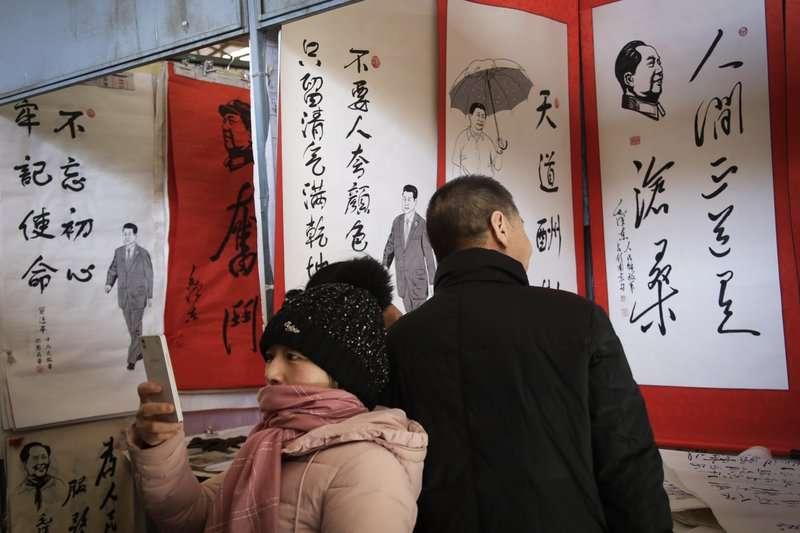北京的市集販賣寫著習近平與毛澤東語錄的字畫。(美聯社)