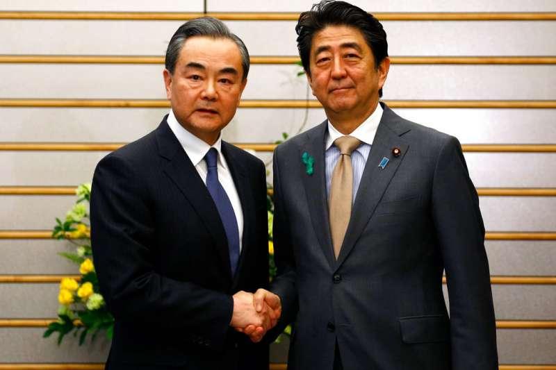 中國外交部長王毅與日本首相安倍晉三。(美聯社)