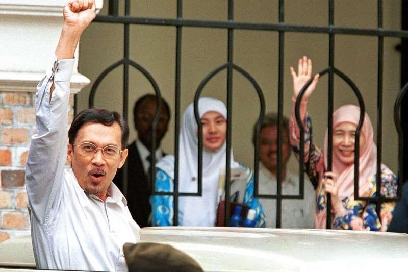 1999年11月12日,離開法院的安華向支持者振臂高呼,他的身後是妻子旺阿芝莎與女兒。