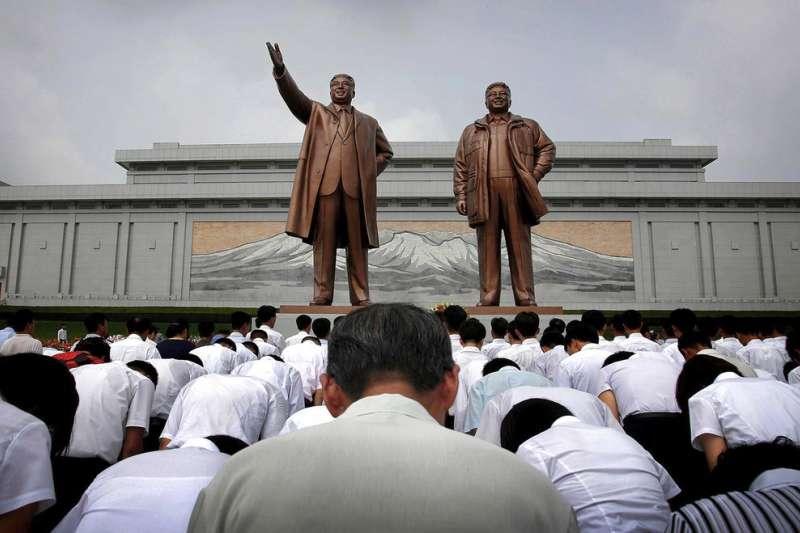 北韓民眾對著金正日(右)與金日成(左)的雕像鞠躬敬禮。(AP)