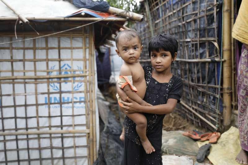 孟加拉難民營中,一名羅興亞小女孩抱著另一個孩子。(美聯社)