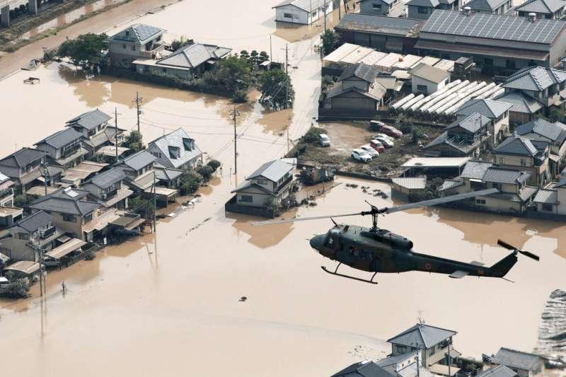 一架直升機正在搜尋待援民眾與災情,只見岡山縣倉敷市泡在泥水之中。(美聯社)