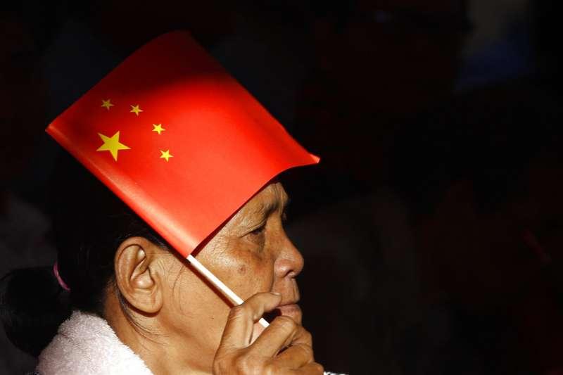 2018年7月2日,柬埔寨總理洪森訪中期間,一名婦人邊聽洪森演說,邊利用中國國旗遮陽。(AP)