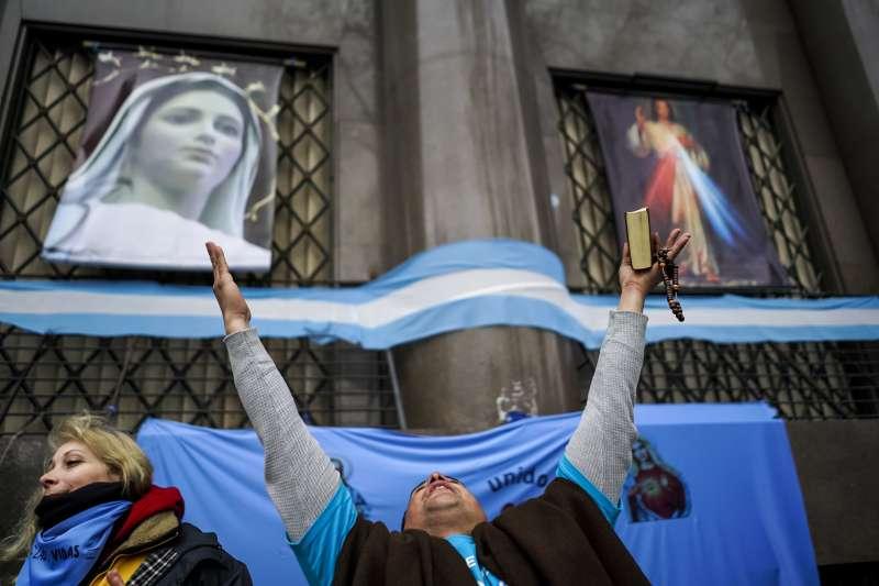 反對墮胎合法化的阿根廷民眾高舉聖母瑪利亞和耶穌基督的畫像(AP)