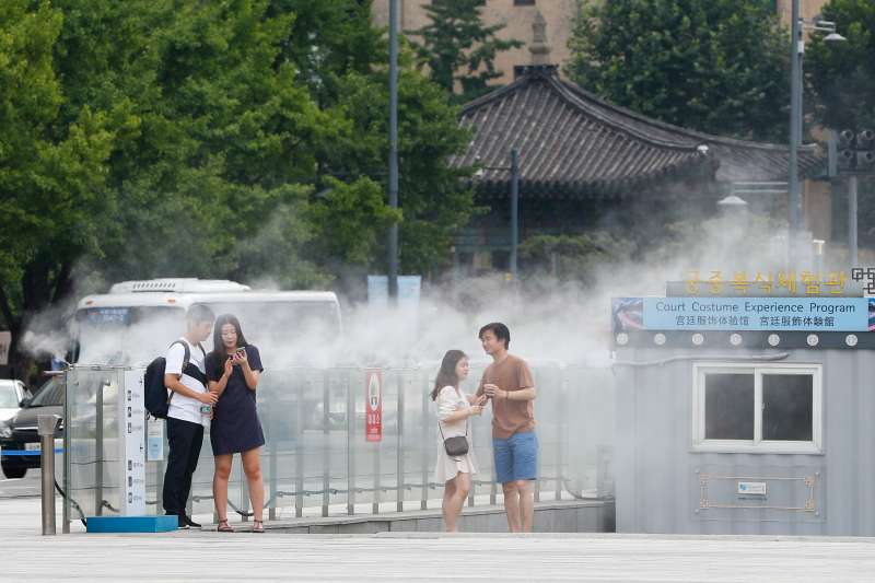 2018年7月27日,兩名兒童在法國巴黎艾菲爾鐵塔旁的噴泉裡戲水納涼(新華社)