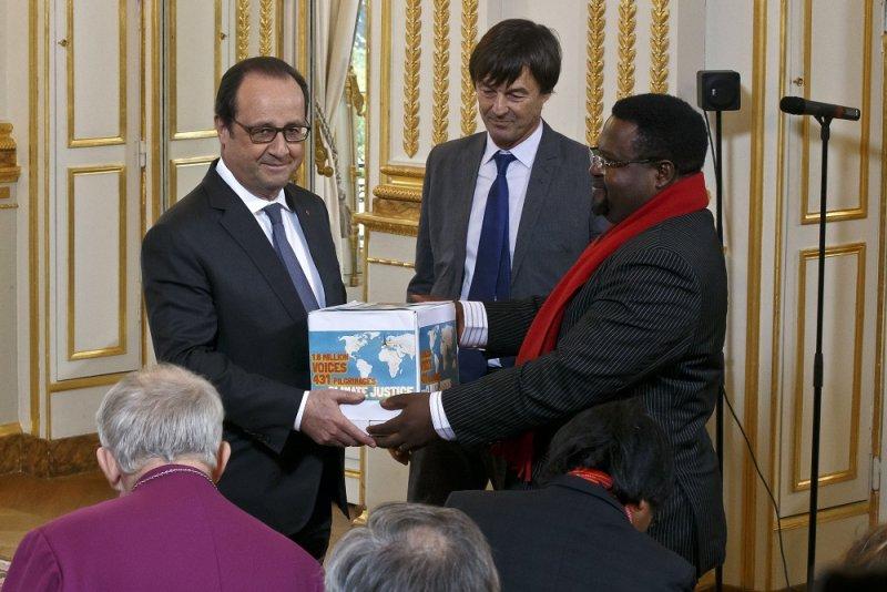 泛非洲氣候正義聯盟的奧古斯汀(右)將裝有國際連署支持氣候協議的盒子交給法國總統奧朗德(左)