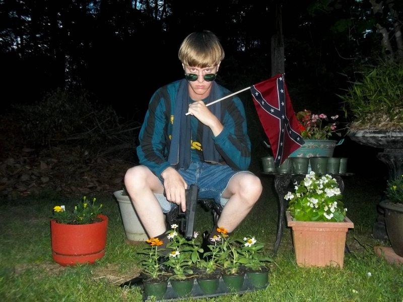 南卡羅來納州教堂屠殺案兇手魯夫左手持邦聯旗、右手持槍的自拍照。(美聯社)