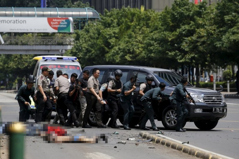 雅加達14日上午發生連環爆炸案,警方在罹難者屍體旁與槍手對峙。(翻攝推特)