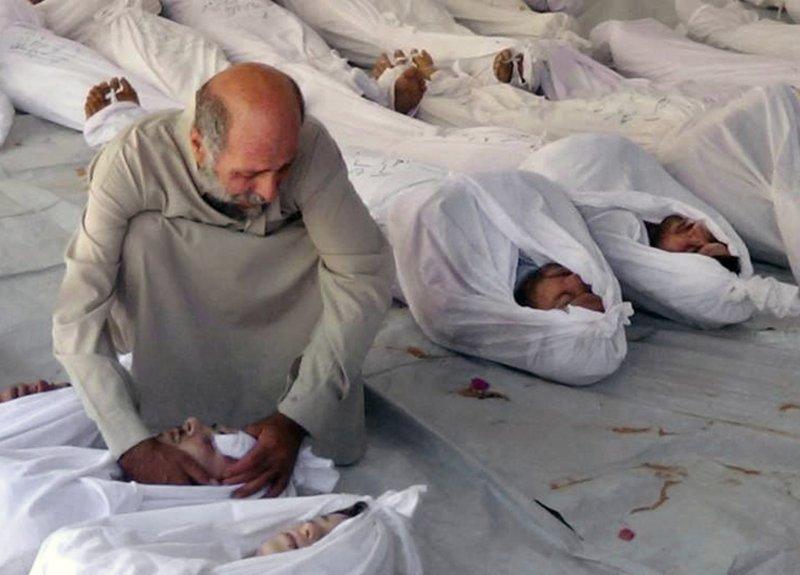 一名敘利亞戰亂罹難者家屬撫屍哀傷。(美聯社)