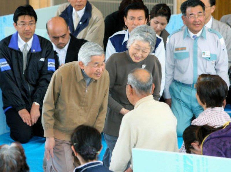 明仁天皇與美智子皇后探望311大地震的災民。(美聯社)
