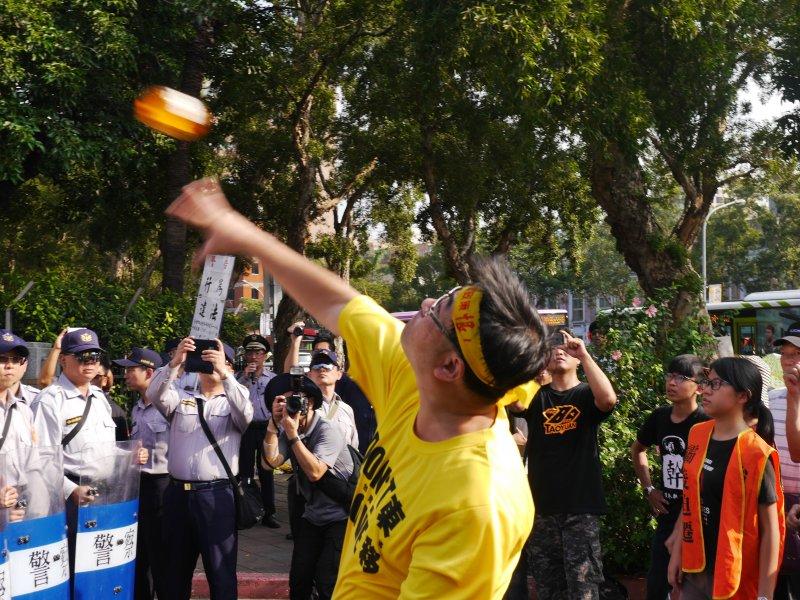 20161028-SMG0045-016-反南鐵東移自救會28日赴政院抗議,陳致曉丟小豬撲滿。(洪與成攝)